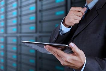 uomo con un tablet in mano e nello sfondo un data center