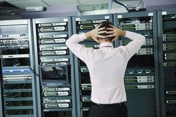 Uomo che guarda un data center con le mani tra i capelli perché non ha un piano di disaster recovery